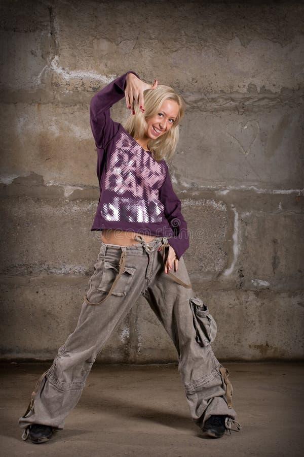 Dança bonita da menina do lúpulo do quadril sobre a parede cinzenta imagem de stock royalty free