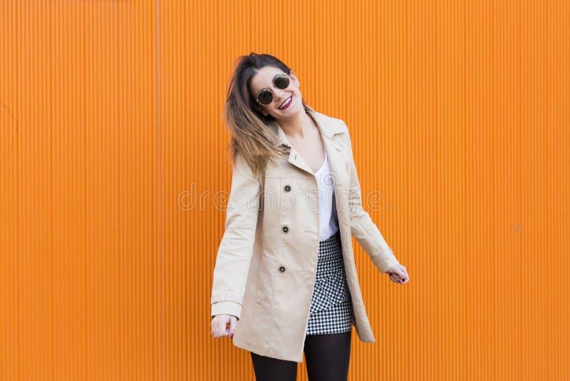 Dança bonita feliz da jovem mulher da forma que sorri sobre a laranja foto de stock