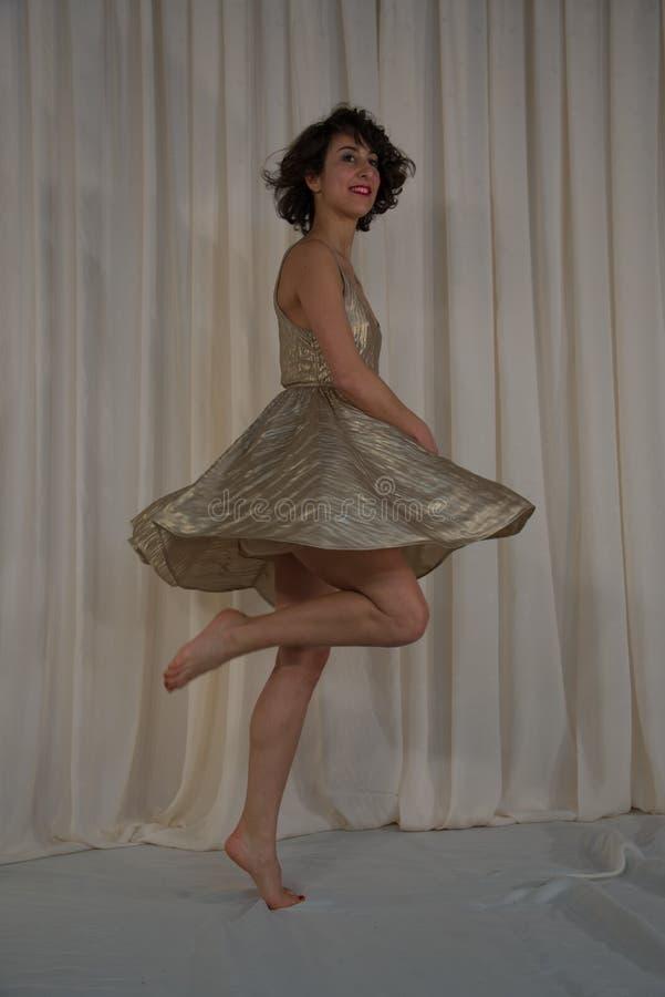 Dança da beleza com saia de vibração Jogo dourado fotos de stock royalty free
