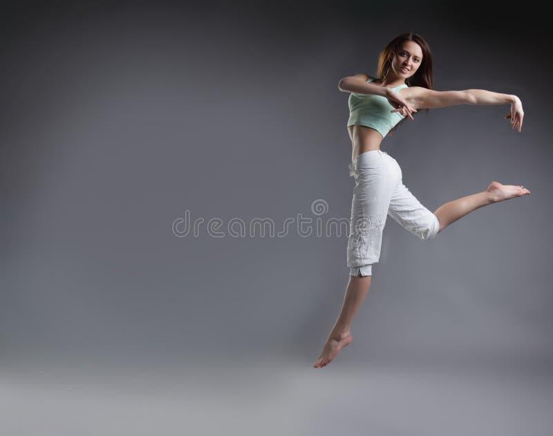 Dança da menina da beleza no fundo cinzento imagens de stock