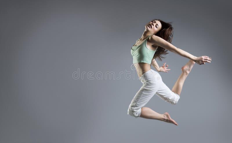 Dança da menina da beleza no fundo cinzento imagens de stock royalty free