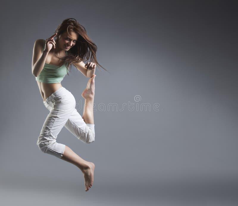 Dança da menina da beleza no fundo cinzento fotos de stock