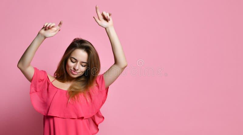 Dança da menina contra a parede cor-de-rosa com sorriso, bom humor de júbilo imagens de stock