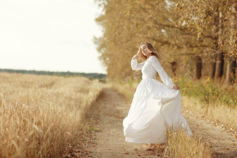 Dança da menina no campo no vestido branco imagem de stock royalty free