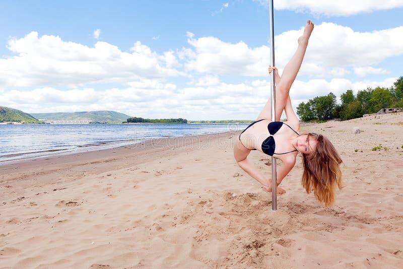 Dança da menina no pilão na praia do verão foto de stock