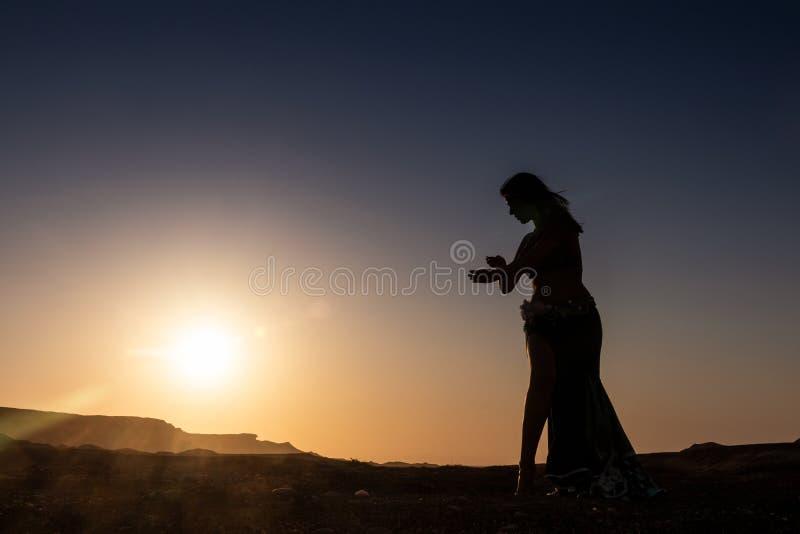 Dança da mulher à dança do ventre árabe famosa Com por do sol na planície árida do deserto de Namibe África angola foto de stock royalty free