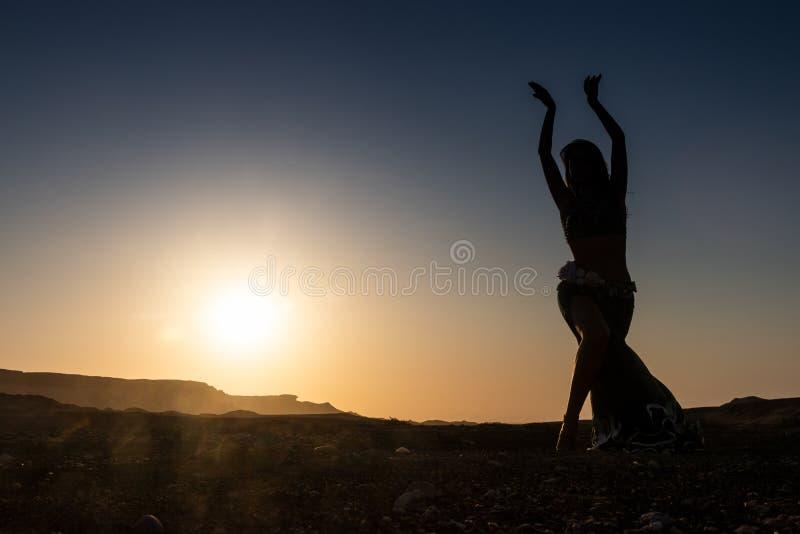 Dança da mulher à dança do ventre árabe famosa Com por do sol na planície árida do deserto de Namibe África angola fotografia de stock