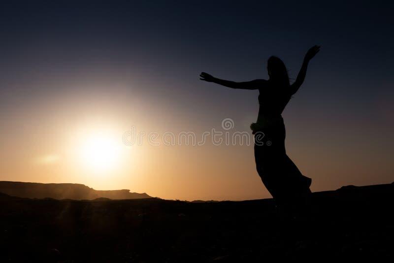 Dança da mulher à dança do ventre árabe famosa Com por do sol na planície árida do deserto de Namibe África angola imagens de stock