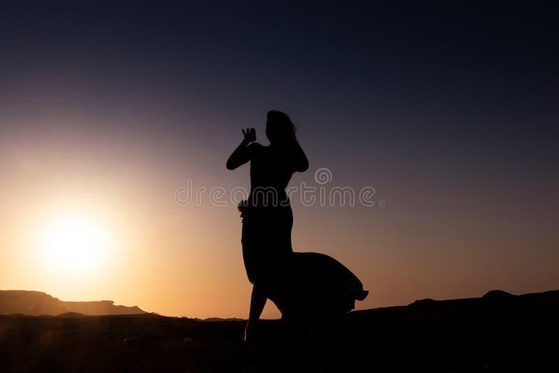Dança da mulher à dança do ventre árabe famosa Com por do sol na planície árida do deserto de Namibe África angola imagem de stock royalty free