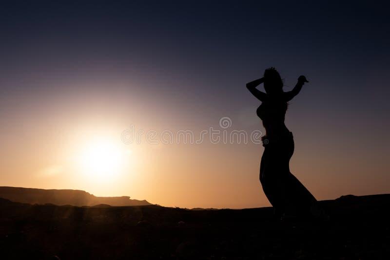Dança da mulher à dança do ventre árabe famosa Com por do sol na planície árida do deserto de Namibe África angola imagem de stock