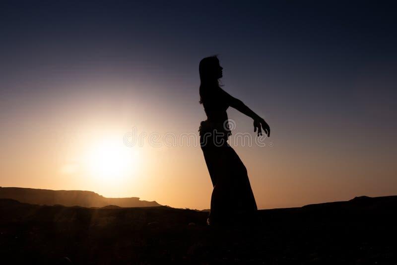 Dança da mulher à dança do ventre árabe famosa Com por do sol na planície árida do deserto de Namibe África angola foto de stock