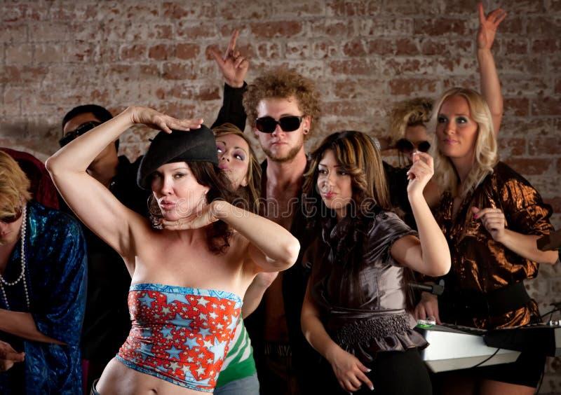 Dança da mulher com os amigos no partido de disco fotografia de stock royalty free
