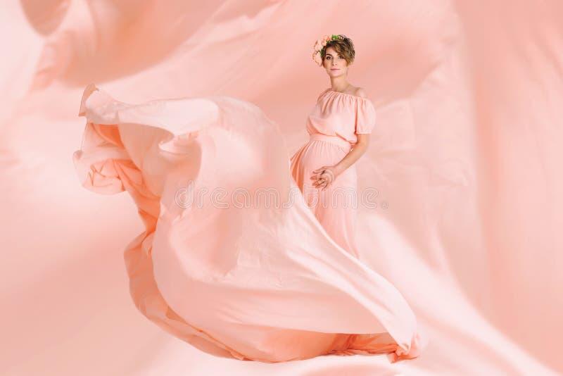 Dança da mulher gravida no voo cor-de-rosa do vestido de noite no vento Tela de ondulação, tiro da forma imagens de stock royalty free