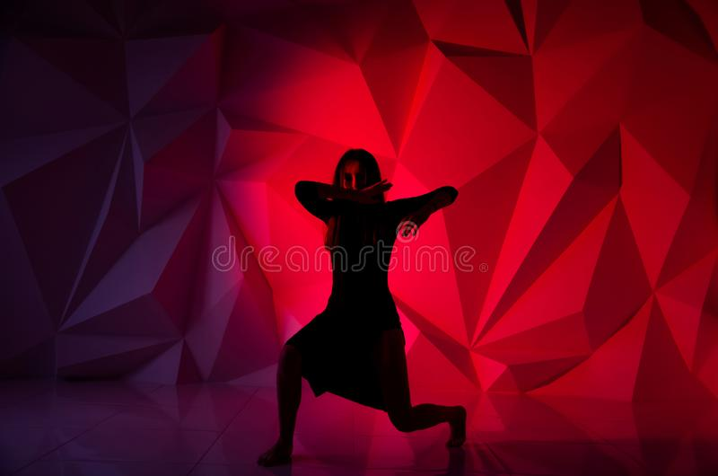Dança da mulher no fundo de uma parede colorido bonita Menina só magro 'sexy' com cabelo preto longo na imagem de stock royalty free