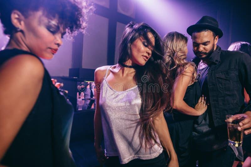 Dança da mulher no partido com os amigos no clube noturno imagens de stock royalty free