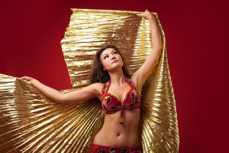 Dança da rapariga com a asa do ouro no vermelho imagens de stock royalty free