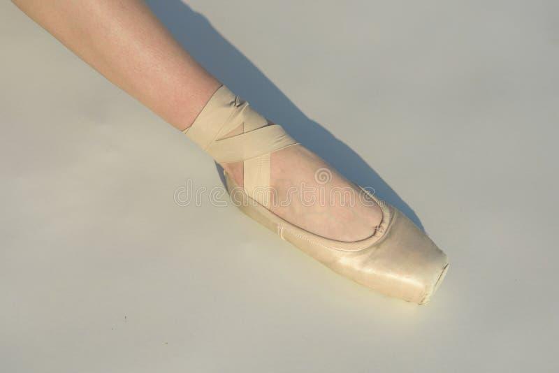 Dança de dedo do pé Pé da bailarina na sapata de bailado branca Atando o deslizador do bailado Foott fêmea na sapata do pointe Sa fotografia de stock royalty free