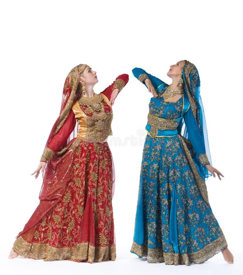 Dança de duas mulheres novas no traje indiano imagem de stock royalty free