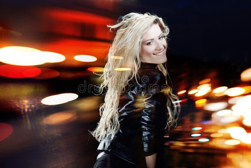Dança de sorriso da jovem mulher, em um fundo preto fotos de stock royalty free
