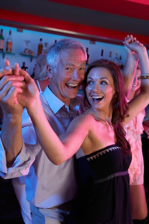 Dança do homem sênior com a mulher mais nova na barra ocupada foto de stock royalty free