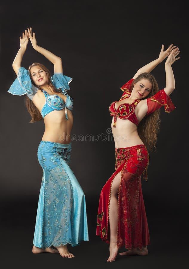 Dança e sorriso de duas mulheres no traje árabe imagens de stock royalty free