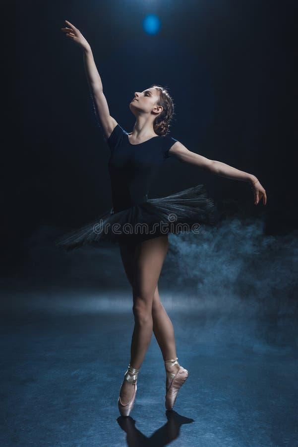 dança elegante atrativa da bailarina em sapatas do pointe e no tutu preto no estúdio foto de stock