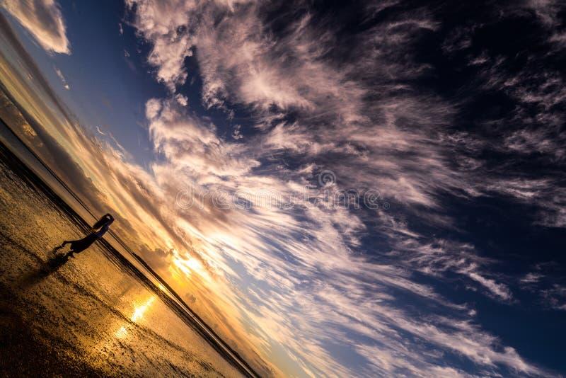Dança fêmea no céu nebuloso da noite na praia foto de stock royalty free
