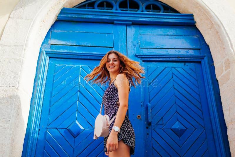 Dança feliz da jovem mulher contra a porta de madeira azul Retrato exterior da menina adolescente bonita que tem o divertimento fotos de stock royalty free