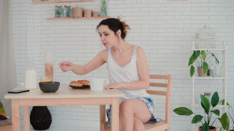 Dança feliz da jovem mulher em pijamas vestindo da cozinha na manhã Menina moreno que tem o divertimento durante o café da manhã foto de stock