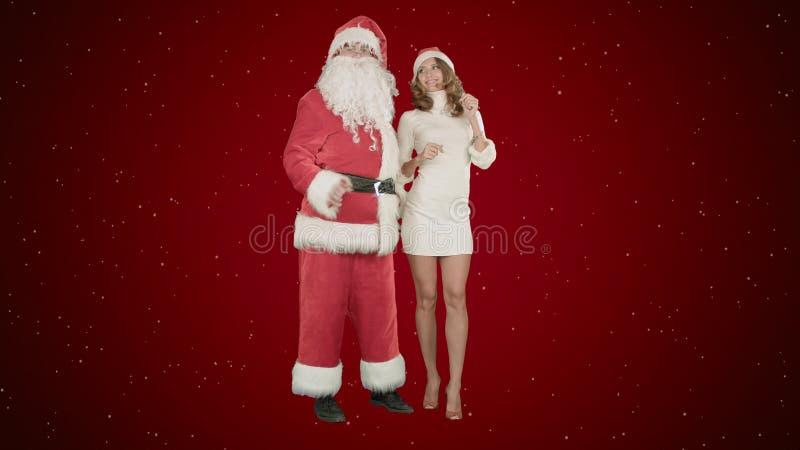 Dança feliz da menina do sorriso do Natal com Santa Claus no fundo vermelho com neve fotografia de stock royalty free