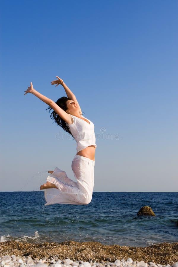 Dança feliz da mulher na praia fotos de stock royalty free