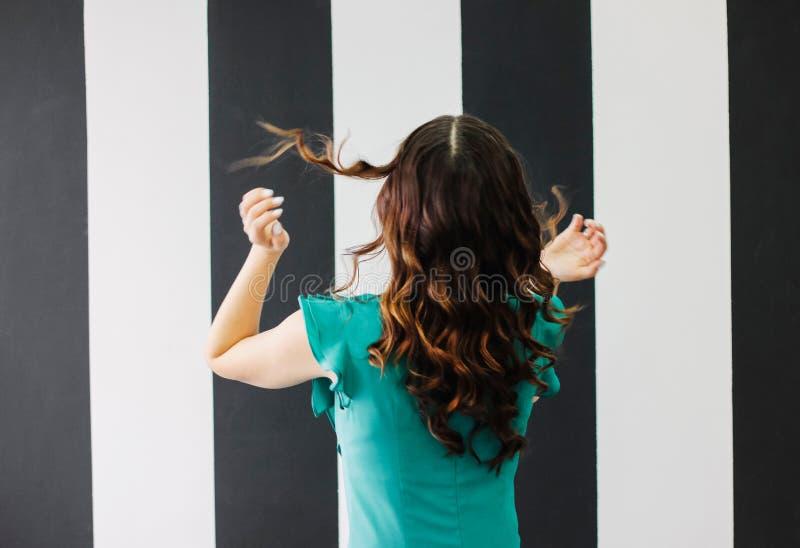 Dança feliz no cabelo encaracolado s da morena encantador bonita do movimento foto de stock