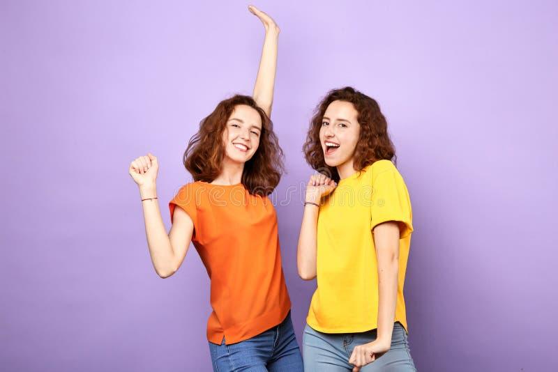 Dança feliz positiva dos gêmeos sobre o fundo azul fotos de stock royalty free