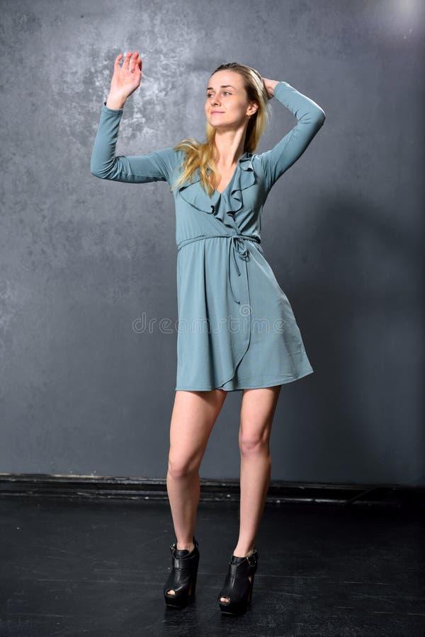 Dança loura da menina em um fundo cinzento da parede foto de stock