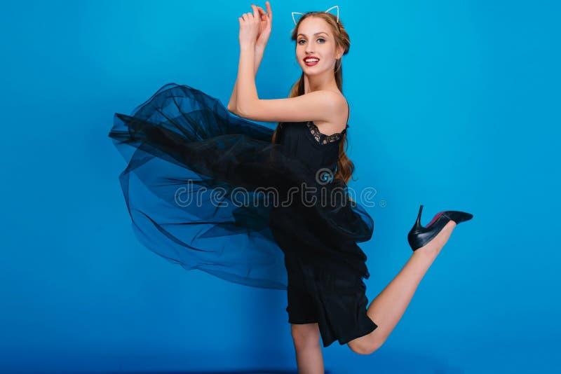 Dança magro da menina no partido, seu vestido bonito que vibra, tem um pé acima Sapatas pretas elegantes vestindo com saltos alto foto de stock royalty free