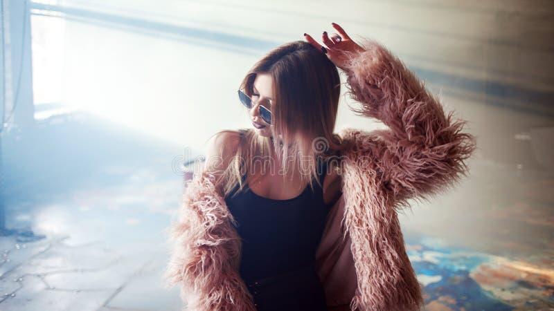 Dança na moda da menina em um revestimento cor-de-rosa macio imagens de stock