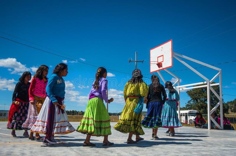 Dança nativa do grupo da menina da escola no vestido colorido tradicional no campo de jogos, cesto, América foto de stock royalty free