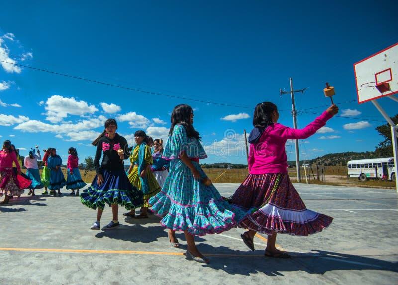Dança nativa do grupo de estudantes da escola no vestido colorido tradicional no campo de jogos, México, América fotos de stock royalty free