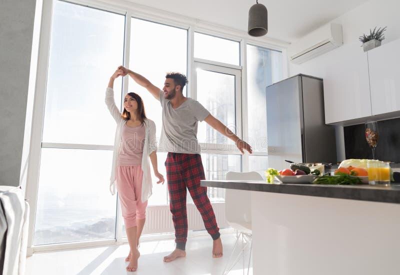 Dança nova dos pares na cozinha, na mulher asiática bonita e no homem do hispânico fotografia de stock