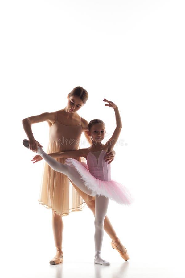 A dança pequena da bailarina com o professor pessoal do bailado no estúdio da dança imagem de stock