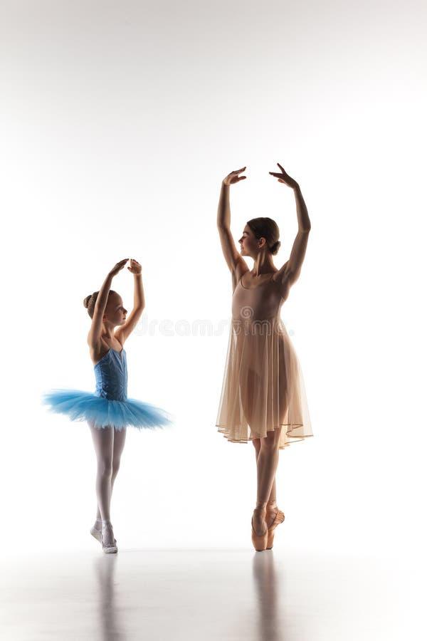 A dança pequena da bailarina com o professor pessoal do bailado no estúdio da dança fotografia de stock