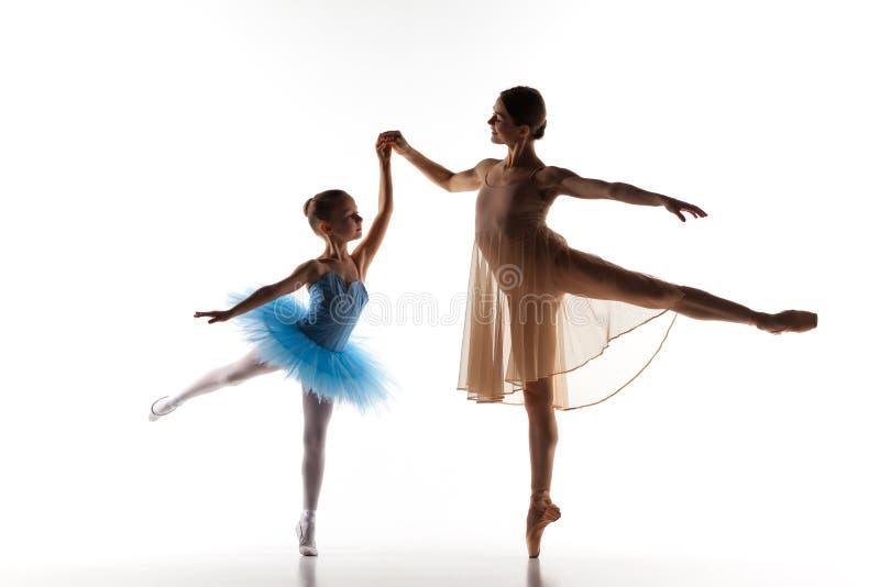 A dança pequena da bailarina com o professor pessoal do bailado no estúdio da dança imagens de stock royalty free