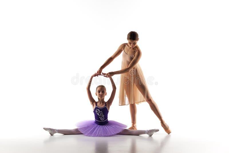 A dança pequena da bailarina com o professor pessoal do bailado no estúdio da dança imagens de stock