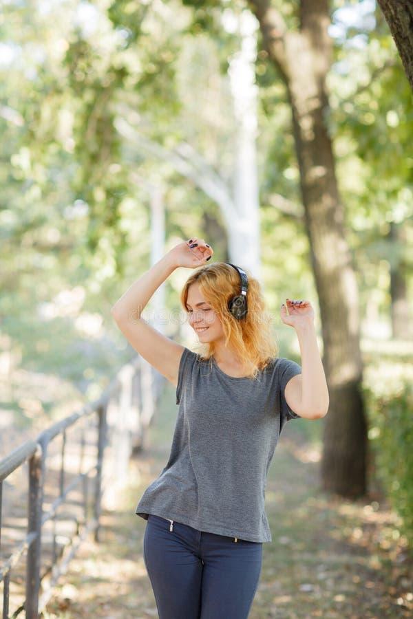 Dança positiva, bonito, sorrindo da menina com fones de ouvido em um fundo do parque Conceito da música Copie o espaço imagens de stock royalty free