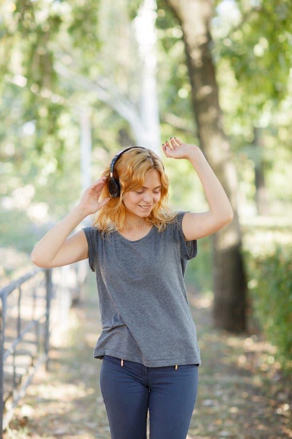 Dança positiva, bonito, sorrindo da menina com fones de ouvido em um fundo do parque Conceito da música Copie o espaço foto de stock royalty free