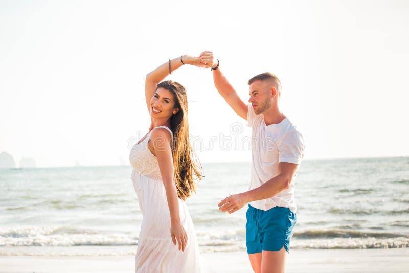 Dança romântica adulta caucasiano feliz e alegre nova dos pares na praia tropical do verão - curso da lua de mel e conceito do la fotos de stock royalty free
