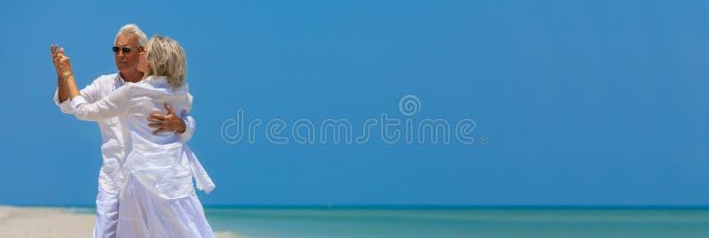 Dança superior feliz dos pares que guardara as mãos em uma praia tropical fotografia de stock
