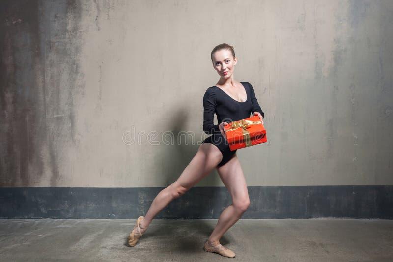 Dançarino ativo do laisure louro da felicidade que mostra a caixa de presente imagem de stock royalty free