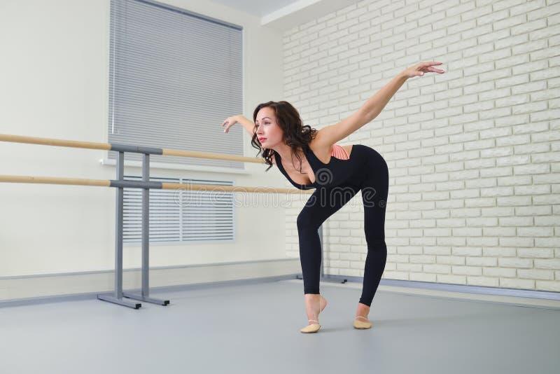 Dançarino bonito da mulher no bodysuit preto que dança graciosamente o bailado no estúdio fotos de stock royalty free