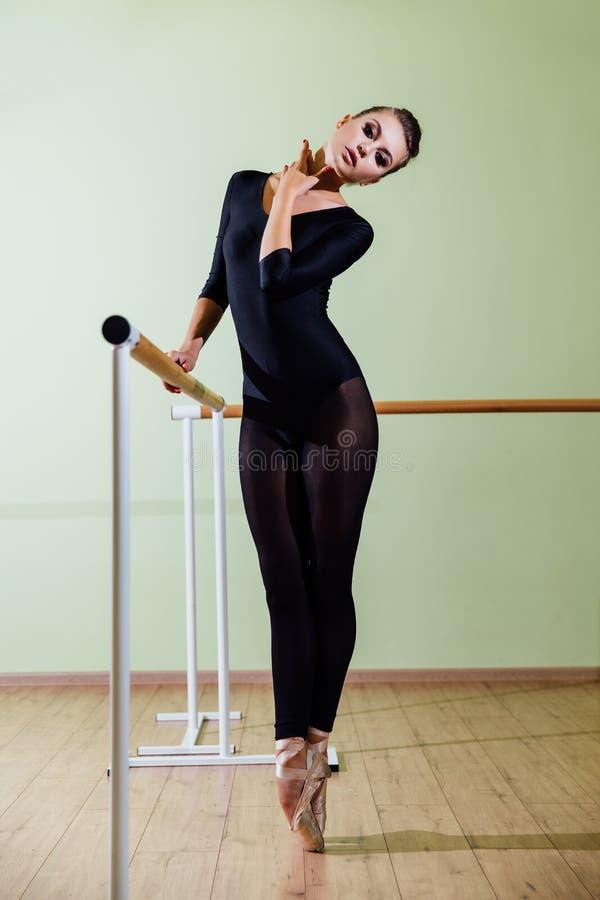 Dançarino bonito novo que levanta na barra do bailado da sagacidade do estúdio na ponta do pé Morena 'sexy' moderna foto de stock royalty free